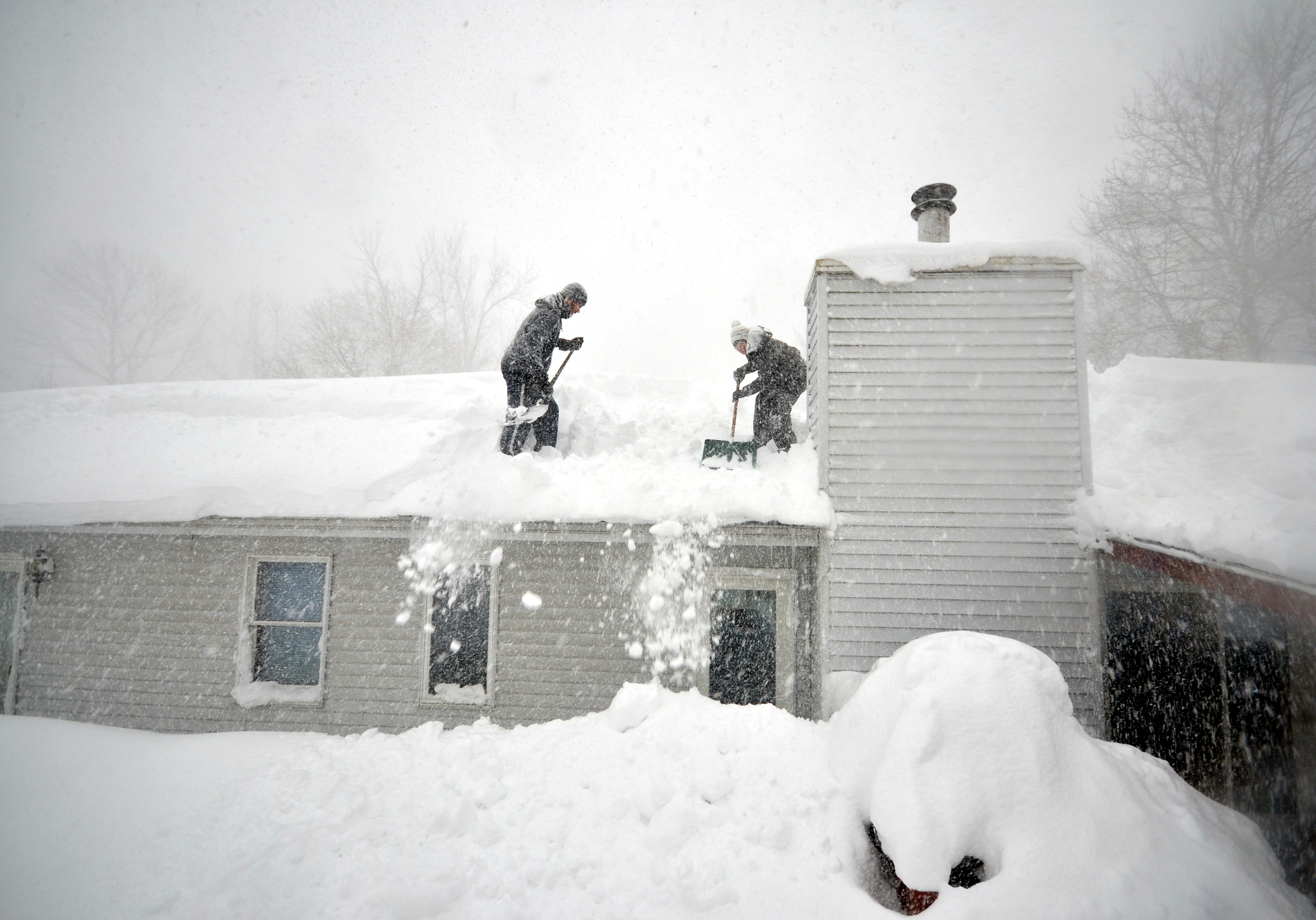 Large amounts of snow covering a house's roof.